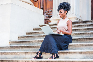 Way to Success. Young African American woman with afro hairstyle wearing sleeveless top, black skirt, sandals, sitting on stairs of vintage office building in New York, working on laptop computer..