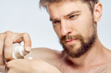 1723738 handsome man squeezes cream on hand on a light background portrait