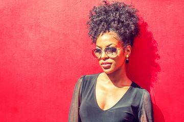 Portrait of Young African American Woman in New York. Young black woman with afro hairstyle wearing long sleeve mesh sheer shirt, sunglasses, standing against red background under sun..