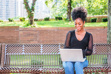 Young beautiful African American Woman with afro hairstyle wearing mesh sheer long sleeve shirt, jeans, sitting on bench at park in New York, looking down, working on laptop computer, smiling..