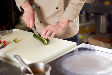 Male chef cutting green zucchini. Zucchini being chopped on white cutting board by male chef. Chef cutting vegetables on cutting board.