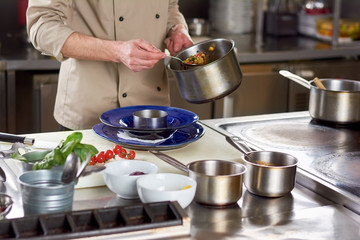 Chef put out with spoon stewing vegetables. Cropped image of male chef going putting garnishing into stainless bowl. Food preparation at professional kitchen.