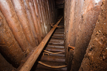 Old abandoned underground mica ore mine shaft tunnel with wooden stands