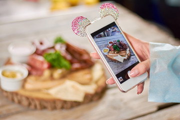Woman taking a photo of grilled sausages. Woman hand using smartphone to take a photo of dish. Woman taking a photo of delicious food with smartphone at restaurant.