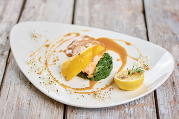 Tasty dish at restaurant table. Delicious salmon with soy caramel sauce on plate. Appetizing dinner on restaurant table.