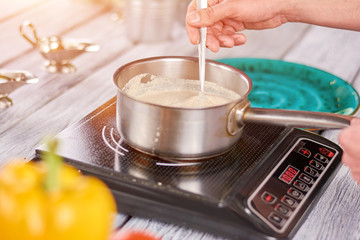 Chef stirring cream soup in stainless pot. Chef cooking cream soup with mushrooms. Cooking cream soup with mushrooms at home, recipe.