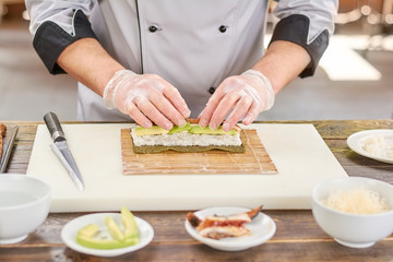 Chef preparing sushi with eel and avocado. Chef hands in disposable gloves cooking sushi at kitchen of japanese restaurant.
