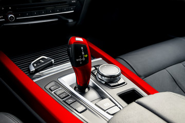 Red automatic gear stick of a modern car, car interior details