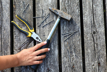 A nice girl takes an old hammer. Nearby are pliers and nails.