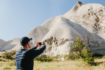 The man in dark clothes takes photo of beautiful rocks on smartphone on warm sunny day in Cappadocia in Turkey.
