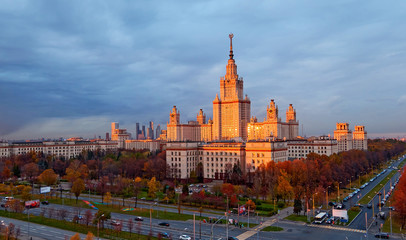 High contrast view of sunset orange color building of Moscow university with glowing reflecting windows, red autumn trees, avenue crossing and heavy lead dramatic sky