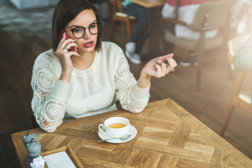 Young businesswoman in glasses and white sweater is sitting in cafe at wooden table and talking on mobile phone. Telephone conversations. Hipster girl relaxing, drinking tea, calling her friends.