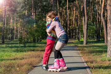 Red-haired girl on roller skates hugging boy in park.