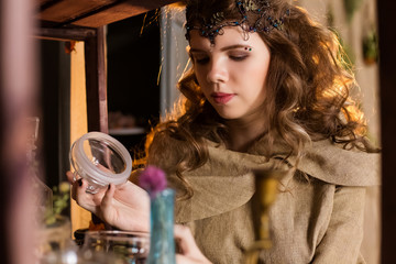 Medieval outfit of a princess, a sorceress, a witch with a hood and a tiara on her head. Beautiful girl teenager, women. Choose the magic ingredients to make a potion.