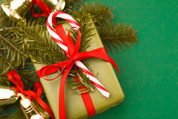 Gift box in green wrapping paper, candy, xmas bells, pine on red background. Copy space. Closeup