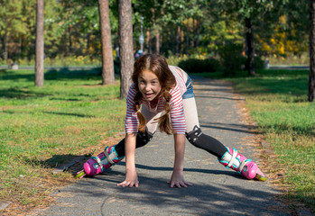 Red-haired girl with braids riding on rollers and falls in the park.