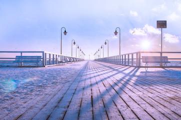 Drewniane molo, pokryte świeżą warstwą śniegu, zimowy poranek.