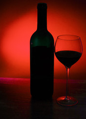 Outlines of wine bottle and glass with wine on red black background