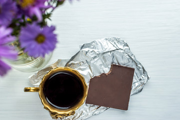cup of coffee with a bouquet of flowers and chocolate on a table
