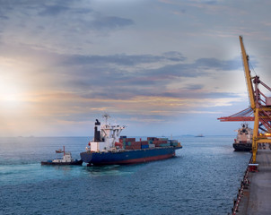 A tugboat pushing a container vessel during berthing at an industrial port.Vessel berth on arrival at port of Thailand.