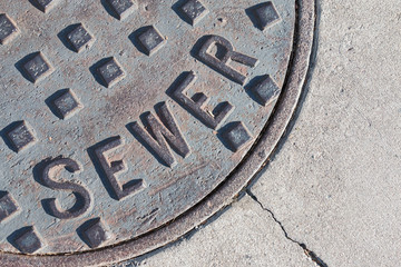 Metal sewer cover in pavement. Section of circular lid with hard shadows on raised lettering.