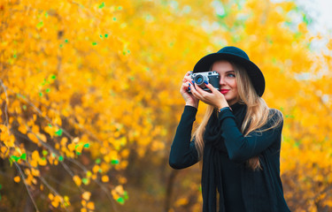 young woman photographing outdoors in autumn. Yellow leaves background