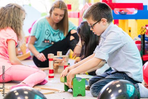 niedliche jungen und m dchen in kindergarten oder vorschule spielen mit holzspielzeug. Black Bedroom Furniture Sets. Home Design Ideas