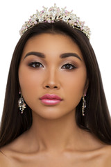 Cute sexy girl with professional makeup, pink crown and earrings looking at the camera, close-up. Beauty and clear skin, make-up concept