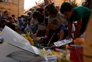 Children place flowers, candles and drawings at a memorial for murdered investigative journalist Daphne Caruana Galizia, who was killed by a car bomb last Monday, in Valletta