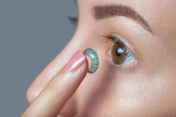 woman holds a blue contact lens on her finger. Eye care and the choice between the means to improve vision.