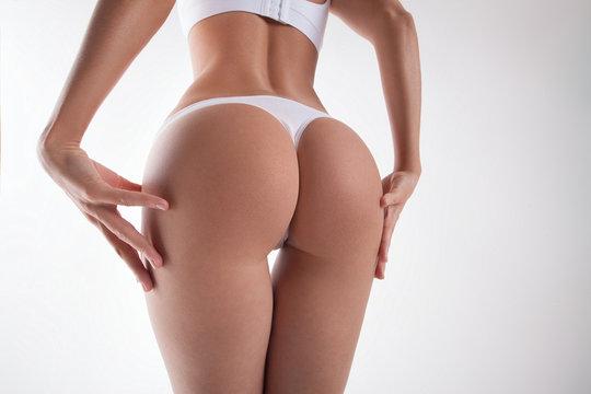Slender round female buttocks close-up