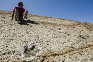 Tourist sitting close to several dinosaur fossil trackways, Sesimbra, Portugal