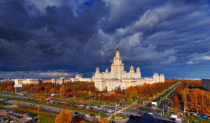 A gradient softened view of sunset building of Moscow university with glowing reflecting windows, red autumn trees, avenue crossing and heavy lead dramatic sky over the campus.