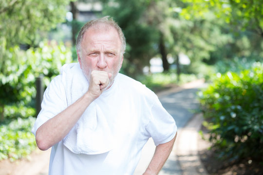 Closeup portrait, senior guy holding towel, very tired, exhausted from over exertion, coughing catching breath, isolated outdoors outside green trees background