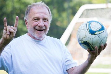 Closeup portrait, elderly man holding up soccer ball and showing off horns sign with hands, isolated soccer goal post outdoors background