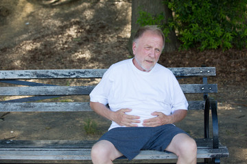 Closeup portrait, old man clutching stomach, having belly pain, sitting on bench, isolated outdoors, green trees background. Full after a meal or pain after walking