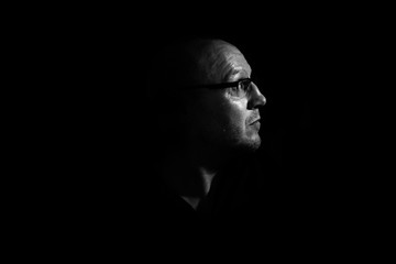 Side profile of a white middle aged man with spectacles or glass in shadow against a black background looking up towards the light