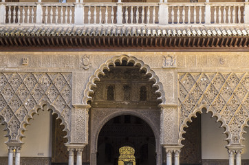Seville, Spain - October 11, 2017: Closeup of the detailed carvings on the walls and arches of the Royal Alcazar