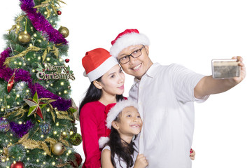 Family taking selfie picture near Christmas tree
