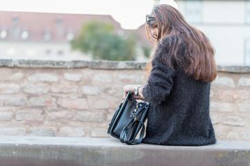 Hübsche junge Französin mit langen Haaren und schwarzer Handtasche in Straßburg