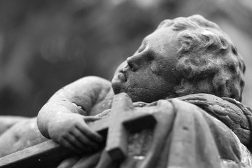 lying stone angel holding the cross in hand, black and white photo