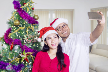 Couple with Christmas tree taking selfie photo