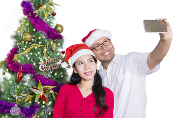Couple making selfie with Santa hat
