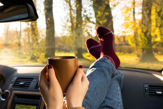 Autumn car trip. Woman feet in warm wool socks and cup of tea in the car