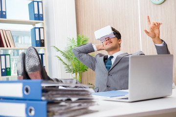 Businessman with VR virtual reality glasses in office