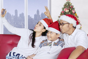 Cheerful family taking selfie with Santa hat