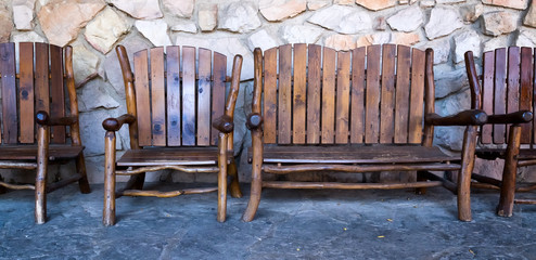 Rustic wood chairs in a row against a stone wall. Banner format