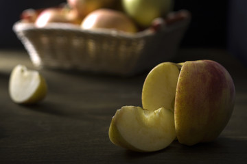 The Apple slices are on the background of the basket of apples.