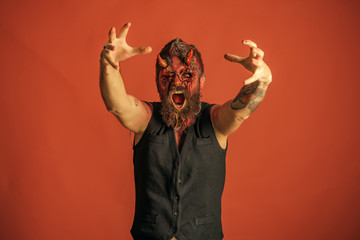 Halloween man devil with zombie hands on orange background