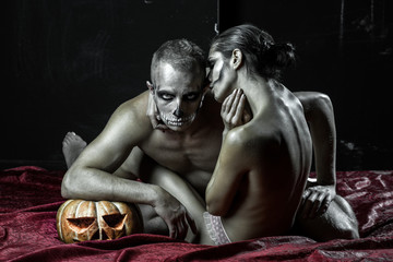 Halloween Man and sexy woman with scary face embrace on bed.